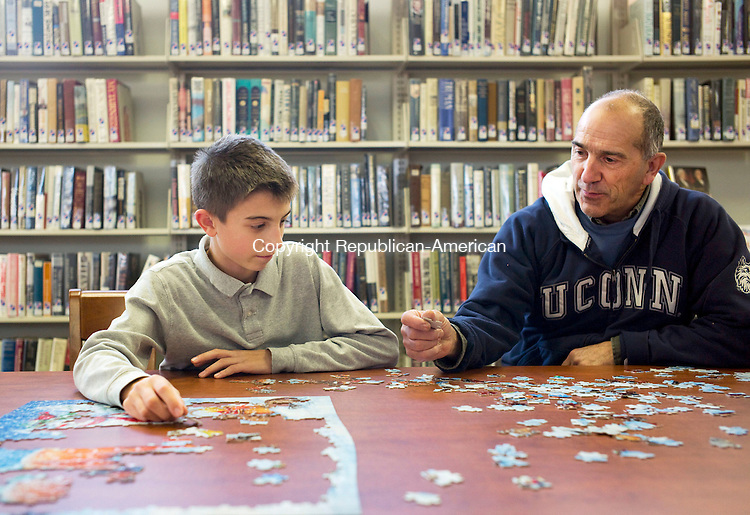 Middlebury, CT- 25 November 2015-112515CM01-  Nathaniel Zembruski, 12, left, of Naugatuck and his grandfather Nick Corsi of Middlebury,  work on a puzzle at the Middlebury Public library on Tuesday.  A calendar of events for the month of December is available at the library.  For more information stop by the library located at 30 Crest Road or contact them by phone at 203-758-2634. Christopher Massa Republican-American