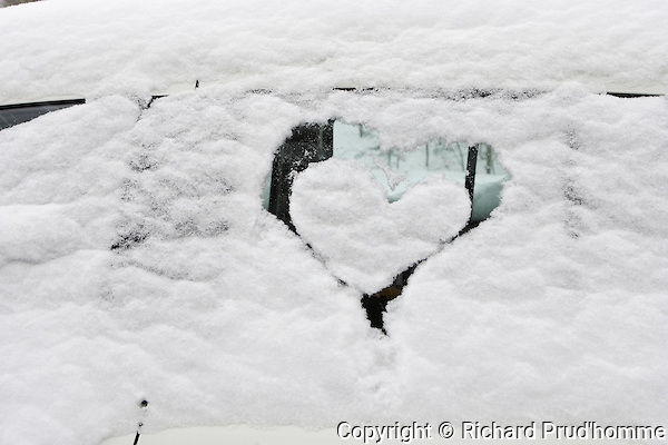 Someone drew a heart in the snow covering a parked car