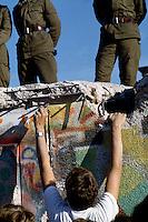 Berlino, 9 Novembre, 1989. Un giovane armato di forchetta si arrampica sul muro di Berlino presidiato da soldati della Germania dell'Est poco prima della sua caduta..Ph. Antonello Nusca/Buenavista photo