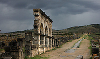 House of Columns on the Decumanus, Volubilis, Morocco, pictured on December 25, 2009. Beneath a cloudy winter sky the road leads past the facade of this impressive ruined house. Around the city fertile plains providing agriculural produce stretch towards the mountains. Volubilis, founded in the 3rd century BC was an important city in the Western part of Roman North Africa. The Romans abandoned it in the 3rd century AD. Excavations were started by the French in 1915, and it became a UNESCO World Heritage site in 1997. Picture by Manuel Cohen