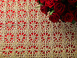 Red Roses on a red and gold tablecloth. Overhead view with copy space.
