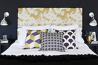 Gold and purple colours bring a sence of opulence to this dark blue bedroom