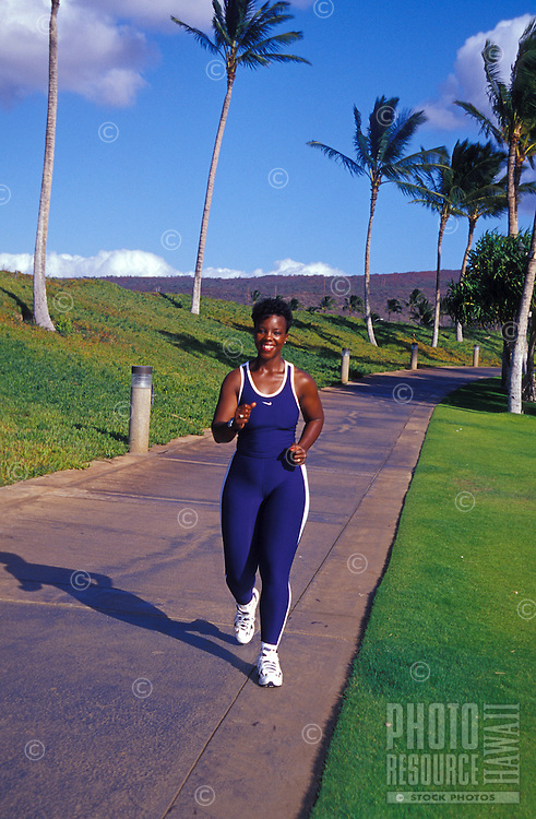 Woman jogging at Ko'olina beach, West Oahu