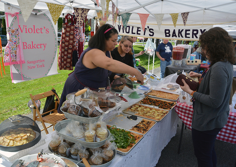 A customer served by Sina Clark, at the Violet's Bakery booth at the Opening Day of the 2017 Saugerties Farmer's Market on Saturday, May 27, 2017. Photo by Jim Peppler. Copyright/Jim Peppler-2017.