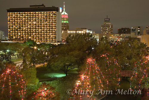 A cityscape of San Antonio, Texas overlooking the famous Riverwalk with the cypress trees draped in Christmas lights.
