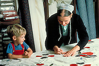 An Amish woman traces a design onto a quilt in a loom as 4 year old boy watches. Amish mother and son. Lancaster Pennsylvania United States Amish home.