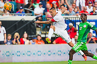 June 07, 2014:   the United States of America forward Clint Dempsey (8) takes a shot on the goal while being defended by Nigeria defender Juwon Oshaniwa (13) during action between the USA Men's National Soccer team and Nigeria at EverBank Field in Jacksonville, Florida.  This is the last match before the USA team leaves for Brazil and the 2014 World Cup Championships. USA defeated Nigeria 2-1.
