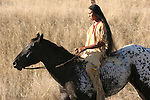 A Native American Indian boy riding bareback on a horse on the prairie of South Dakota