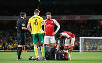 Christoph Zimmermann of Norwich City & Olivier Giroud of Arsenal look concerned as Ainsley Maitland-Niles of Arsenal receives treatment on an injury during the Carabao Cup match between Arsenal and Norwich City at the Emirates Stadium, London, England on 24 October 2017. Photo by Carlton Myrie.