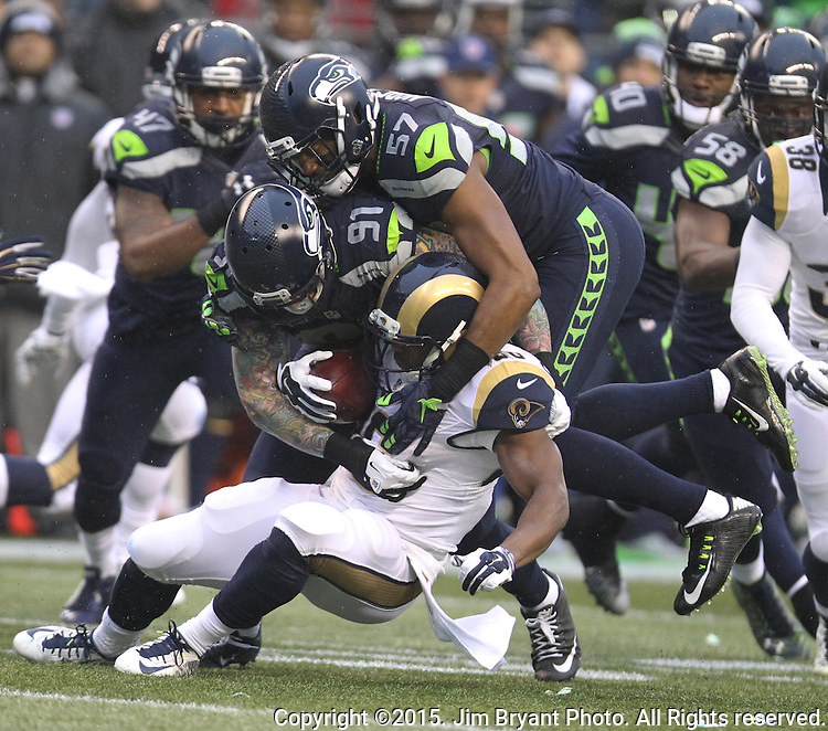 Seattle Seahawks defense, Cassius Marsh (91) and Mike Morgan (57) team up to tackle St. Louis Rams running back Benny Cunningham (36) at CenturyLink Field in Seattle, Washington on December 27, 2015.  The Rams beat the Seahawks 23-17.      ©2015. Jim Bryant Photo. All Rights Reserved