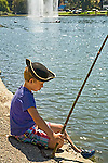 Blonde six year old male wearing pirate hat stares into water and holds fishing pole and sits on edge of lake with shooting fountain.