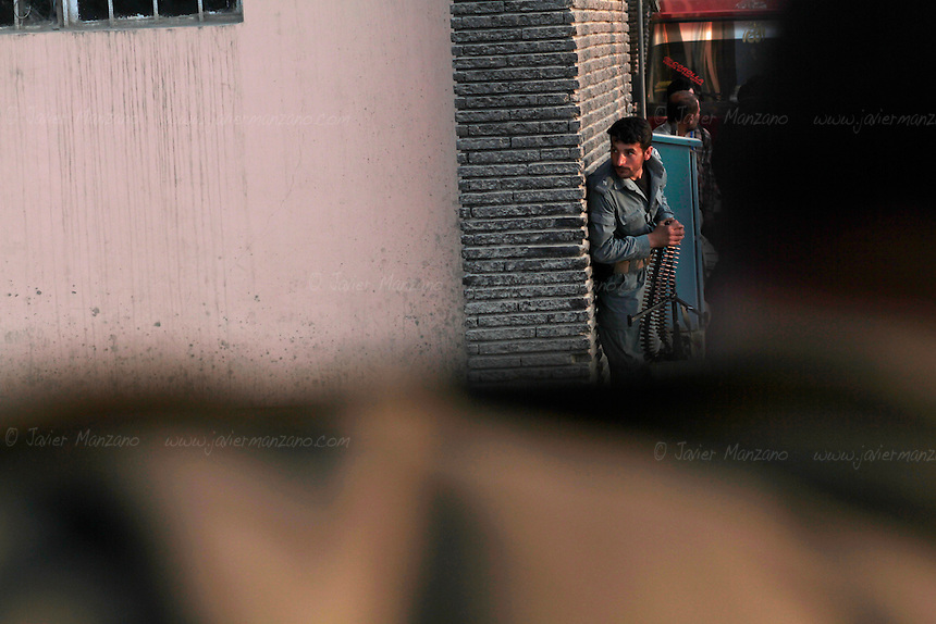 Afghan Security Forces peek through a corner onto a building where suspected insurgents launched one of many gun battles in Kabul today. Heavy weapons fire and rocket-propelled explosions could be heard across the Afghan capital city of Kabul on April 15th, 2012. ..Several targets were hit by alleged insurgents in and around the Shahre Naw and in Shash Darak areas of Kabul, where at least one rocket/mortar impacted the vicinity of the International Security Assistance Forces Headquarters. Heavy gunfire and explosions detonated around the Kabul Star Hotel and Azizi Bank (close to ISAF HQ). The gunfire began when an unconfirmed number of insurgents drove an SUV through the doors of a 5-story building (currently under construction) and used it as a base to launch attacks on ANSF and Norwegian Military Forces (who came to assist the Afghan Security forces). Casualties include one ANSF dead, four ANSF injured and an IMF wounded. ..It has further been confirmed that besides the attack at the Parliament complex earlier in the afternoon, ANSF interdicted a second tier attack in the vicinity of the 2nd Vice-President's residence and arrested two AOG equipped with BBIEDs and another infantry operative in the location..According to an ISAF press release, the attacks, which were concentrated in three clusters around the city, were  labeled  by the Taliban as the start of the so-called ?Spring Offensive? and were largely ineffective. .The attacks began just before 2:00 p.m. and consisted primarily of RPG and small arms fire.  Afghan Crisis Response Units along with Afghan police  and Army forces deployed to repel the attacks that resulted in light casualties while killing or capturing many of  the  suicide attackers in a matter of hours...National Directorate of Security announced that they had captured two suicide bombers alive before they were able to reach their intended targets. ..ISAF quick reaction forces were prepared to respond if required but were not needed.