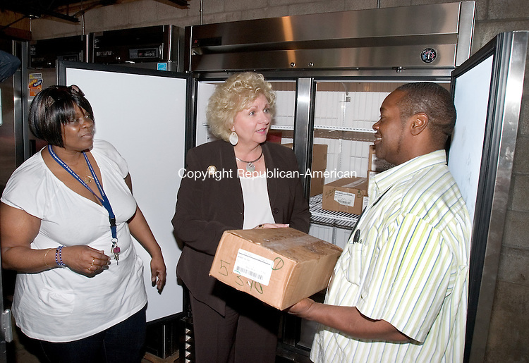 WATERBURY, CT. 27 May 2010-052710SV03--Caren Bouchard of the Naugatuck Savings Bank Foundation, center talks with Regina Suggs, head chef, left, and John West, food pantry coordinator, right, about the new freezer at the Greater Waterbury Interfaith Ministries soup kitchen in Waterbury Thursday. The Foundation donated $5000 to purchase the new double door freezer. <br /> Steven Valenti Republican-American