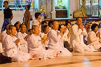 Myanmar, Burma.  Shwedagon Pagoda, Yangon, Rangoon.  Thai Pilgrim nuns praying.