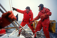 Man points to a safe harbor as another controls the rudder as they sail up the Inside Passage of Canada. MR