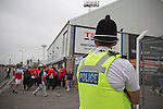 A police officer watching on as supporters of Hartlepool United and Middlesbrough make their way to the Victoria Ground, Hartlepool, before the pre-season friendly between the two teams. Hartlepool were relegated to League Two at the end of the 2012-13 season whilst their Teesside neighbours remained two divisions above them in the Championship. The game ended in a no-score draw, the home team's goalkeeper Scott Flinders saving a second-half penalty from Boro's Lucas Jutkiewicz, watched by a crowd of 2307.