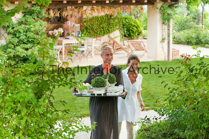 Maddalena Caruso with a friend carrying a tray with decorations for an al fresco dinner table through her garden