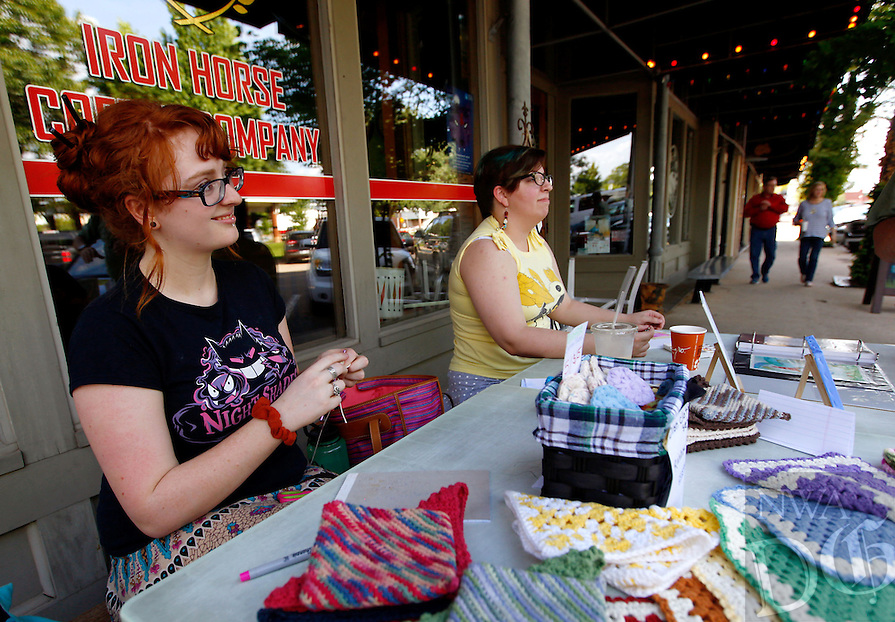 STAFF PHOTO JASON IVESTER --06/20/2014--<br /> B'ney (cq) Landis (left) of Gentry and Cierra (cq) Helms of Rogers work on their crochet and painting arts, respectively, on Friday, June 20, 2014, outside the Iron Horse Coffee Company in downtown Rogers. Mainstreet Rogers hosted their 3rd Friday themed Taste of Summer in downtown Rogers.