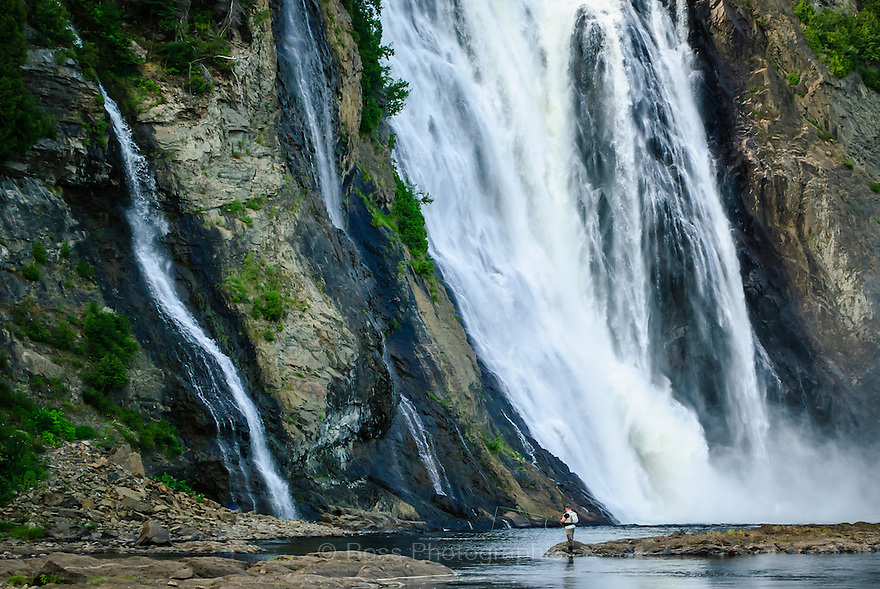 Man fishing at the base of Montmorency Falls, Quebec Canada