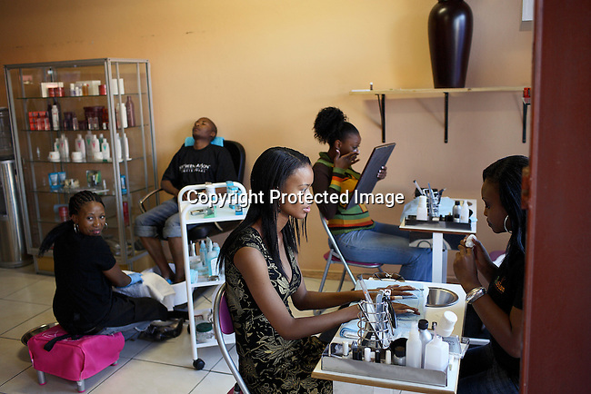 Dorah Mtetwa (c) , age 22, an university student does her nails at an exclusive beauty spot and spa.