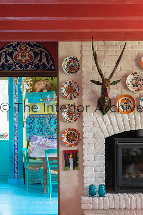 A glimpse into the turquoise-painted kitchen from the wood-burning stove in the sitting room