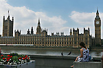 A tourist sits across from Big Ben and the Houses of Parliament on the river Thames in London .22nd July 2012. Photo Steve Christo.