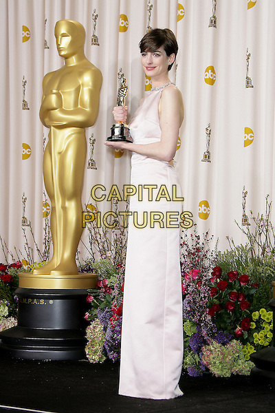 Anne Hathaway (wearing Prada).85th Annual Academy Awards held at the Dolby Theatre at Hollywood & Highland Center, Hollywood, California, USA..February 24th, 2013.pressroom oscars full length pink sleeveless silk satin dress award trophy winner side .CAP/ADM.©AdMedia/Capital Pictures.