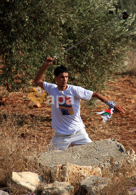 A Palestinian youth hurls stones towards Israeli soldiers during a protest against Israel's separation barrier as masked Palestinian stones throwers clash with Israeli soldiers in the West Bank village of Bilin, near Ramallah, on November 12, 2010. Clashes erupted during the weekly demonstrations, which are aimed at halting the construction of Israel's controversial separation barrier that is mostly built inside the occupied territory and cuts off farmers from their land in border communities like Nilin. Photo by Wagdi Eshtayah