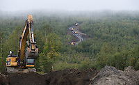Four Cruz Construction rock trucks make their way to a material site on Tofty Road near Manley Hot Springs on Wednesday, August 20, 2014. Cruz Construction began the two year 'Road to Tanana' project in July.