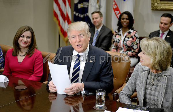 United States President Donald Trump flanked by Education Secretary Betsy DeVos  (R) speaks during  a parent-teacher conference listening session in the Roosevelt Room of the White House on February 14, 2017 in Washington, DC. Photo Credit: Olivier Douliery/CNP/AdMedia
