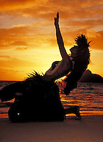 Hawaiian woman in traditional dress performing a ritual hula dance at the beach. Hawaii
