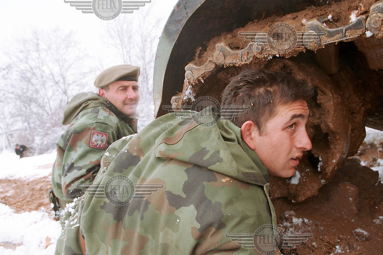 Serb soldiers hide behind a tank near the village of Bukos after coming under fire from the KLA..Kosovo, 23/02/99.