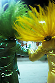 Rio de Janeiro, Brazil. Carnival; two samba dancers holding hands wearing shiny suits and feathers, one yellow the other green.