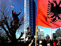 More US and Albanian flags on parade with the statue of Skanderbeg (1405-1468) in the background.