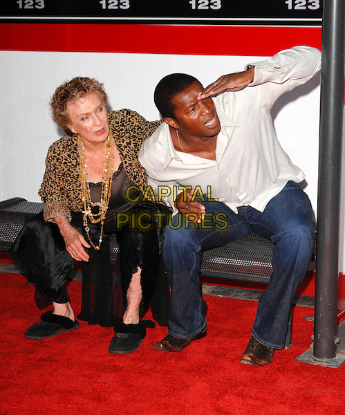 "CLORIS LEACHMAN & ROGER CROSS.The premiere of ""The Taking of Pelham 1 2 3"" at Mann Village Theatre in Westwood, California, USA. .June 4th, 2009  .full length black trousers flared wide leg brown leopard print top jacket gold necklaces slippers sitting funny leaning bending hand jeans denim white top bus stop shelter .CAP/ROT.©Lee Roth/Roth Stock/Capital Pictures"