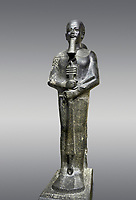 Ancient Egyptian statue of the god Ptah, granodiorite, New Kingdom, 18th Dynasty, (1390-1353 BC)Karnak. Egyptian Museum, Turin. Grey background.<br /> <br /> The statue of the god Ptah is in the likeness of the reigning king Amenhotep III with a youthful almost feminine face, full cheeks, large smiling mouth and fleshy lips. The large almond shaped eyes are characteristic of the period as is the outline of the lips, Drovetti collection. Cat 86