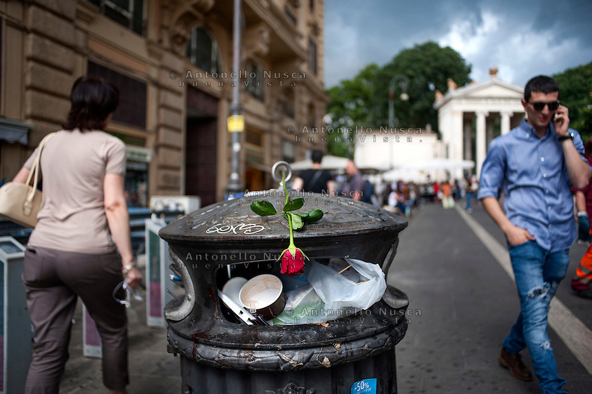 Una rosa gettata sopra un cestino dei rifiuti pieno di spazzatura a Piazzale Flaminio<br /> A red rose abandoned on a garbage can in downtown