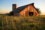 Red barn with silo at sundown, untilled field, on the Great Plains of southwest Iowa.