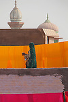 A woman inspects rows of recently dyed fabric drying in the sun on a rooftop in Bikaner.