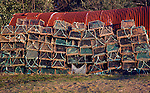 Lobster pots piled against rusty shed, Bawdsey, Suffolk, England
