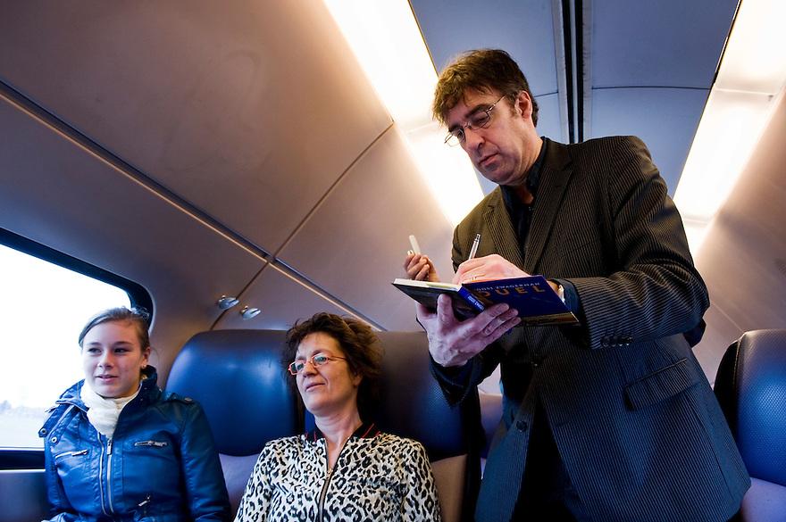 Nederland, Utrecht, 14 maart 2010.Joost Zwagerman, auteur van het boekenweekgeschenk, controleert vervoersbewijzen in de trein. Vandaag geldt het boekenweekgeschenk als treinkaartje. Zwagerman signeert alle boeken, de conducteur zet vervolgens zijn knipje in het boek...Foto Michiel Wijnbergh
