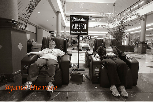 """Jill McDowell takes her son Drew out to the mall after his dentist appointment. Drew and Jill find comfort in two shiatsu chair massages at the Montgomeryville Mall. The perfect stimulation and relaxation for both Drew and Jill. """"Drew and I love coming here. If I fall asleep wake me up in a bit. I think it's important for the boys to get out into the community as much as possible,"""" says Jill. """"I can't just stay in the house all day nor can Drew. I can't imagine what it must be like for him doing the same old thing all the time. This past year we've had a lot of fun."""" Stimulating an autistic child to different environments, exposes the individual to sights, sounds and feelings. This may help to encourage the brain to trigger the right responses. It's important to integrate an autistic child into the community, to encourage development of his social skills at whatever level he is capable. photo by jane therese"""