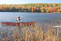 A canoeist paddles the Wenonah Wilderness solo canoe in fall.