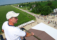 "Clark Lupkes of the Kesley  Ag Center watches RAGBRAI riders roll into Kesley from atop an 80-foot tower over a fertilizer leg building on Wednesday.  ""For a town of 80 people, to have 10,000 bikers come through, it's just incredible,"" he said."