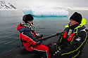 Norway, Svalbard, tourists sitting in Zodiak while floating near iceberg