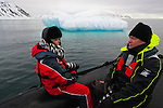 Norway, Svalbard, tourists sitting in Zodiak while floating near iceberg