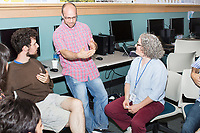 Justin Solomon (red plaid center) speaks with Assaf Bar-Natan (left) and Megan Gall at the Metric Geometry and Gerrymandering Group (MGGG) hackathon at the Data Lab in the Tisch Library at Tufts University in Medford, Massachusetts, USA, on Thurs., Aug. 10, 2017. Solomon is the organizer of the hackathon and an Assistant Professor in MIT's Computer Science and Artificial Intelligence Laboratory (CSAIL) and Department of Electrical Engineering and Computer Science (EECS). Bar-Natan, 24, of Toronto, Ontario, Canada, is a Ph.D. student in Mathematics at the University of Toronto and is the summer intern of the MGGG.  Gall is a Social Scientist at the national Lawyers' Committee for Civil Rights Under Law. The hackathon is part of the first in a series of Geometry of Redistricting workshops put on by the MGGG. Academics, Geographic Information Systems (GIS) professionals, and legal professionals worked together to build tools useful in analyzing voting district data around the country.