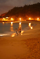 Three boys stand on the beach after sundown. Waimea bay on the North Shore of Oahu.