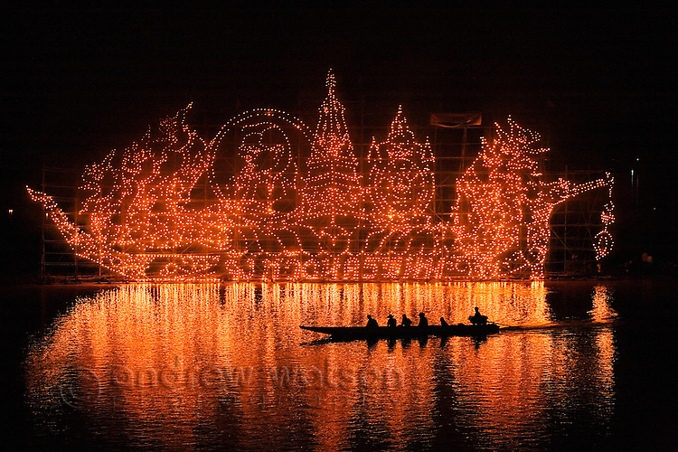 A longtail boat is silhouetted against the glow of a Fire Boat during the Illuminated Boat Procession.  The fire boats are giant bamboo towers decorated with lanterns in religious motifs and set adrift on the Mekong.  Nakhon Phanom, Nakhon Phanom, THAILAND