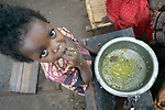 Two-year old Jennifer Angel enjoys the last of her family's meal in a camp for more than 5,000 displaced people in Riimenze, in South Sudan's Gbudwe State, what was formerly Western Equatoria. Families here were displaced at the beginning of 2017, as fighting between government soldiers and rebels escalated.<br /> <br /> Two Catholic groups, Caritas Austria and Solidarity with South Sudan, have played key roles in assuring that the displaced families here have food, shelter and water.<br /> The camp formed around the Catholic Church in Riimenze as people fled violence in nearby villages for what they perceived as the safety offered by the church.